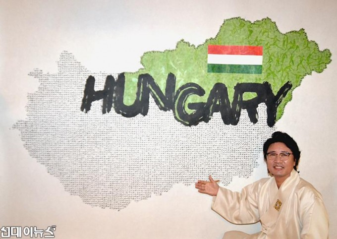 한한국 세계평화작가가 38번째 국가, 헝가리 평화지도을 완성하고 작품설명을 하고 있다(사진=세계평화사랑연맹 제공).JPG